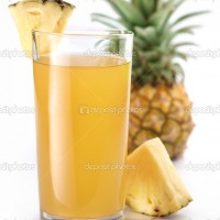 Full glass of fresh pineapple juice and pineapple fruit on the back.